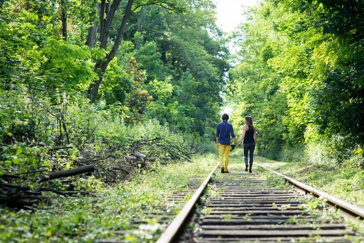 couple marchant sur une voie ferrée abandonnée