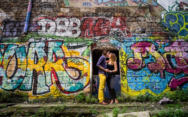 couple s'embrassant devant un mur de graffitis