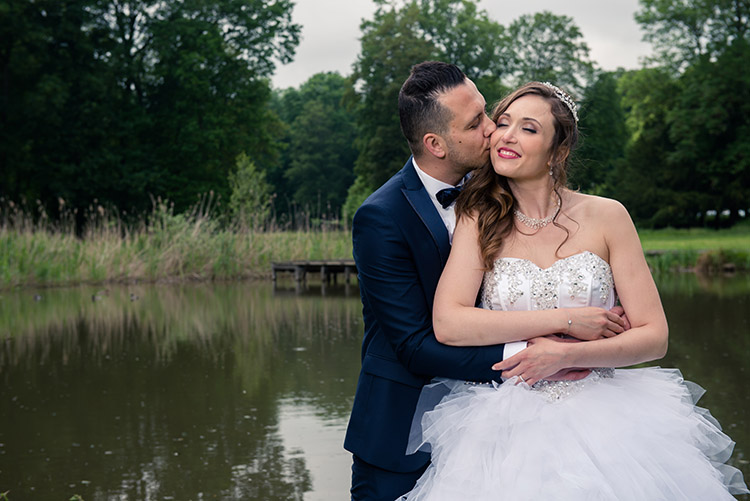lles mariés posant devant le lac du chateau