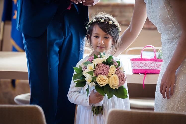 la nièce des mariés tient le bouquet de fleur de la mariée